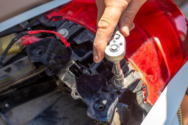 Reparação e desmontagem de uma motocicleta. um homem desenrosca os fechos do porta-malas com uma chave de caixa.