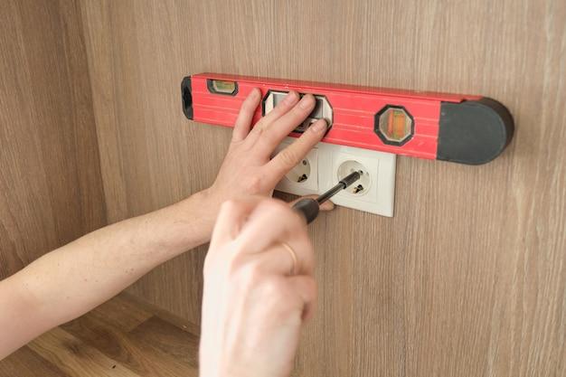 Reparação e instalação de móveis, mãos de eletricista instalando tomadas em móveis utilizando chave de fenda e nível