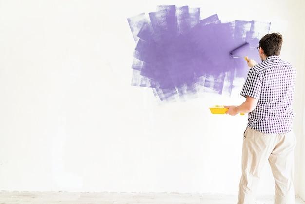 Reparação e melhoria da casa. homem colorindo a parede de roxo com um rolo