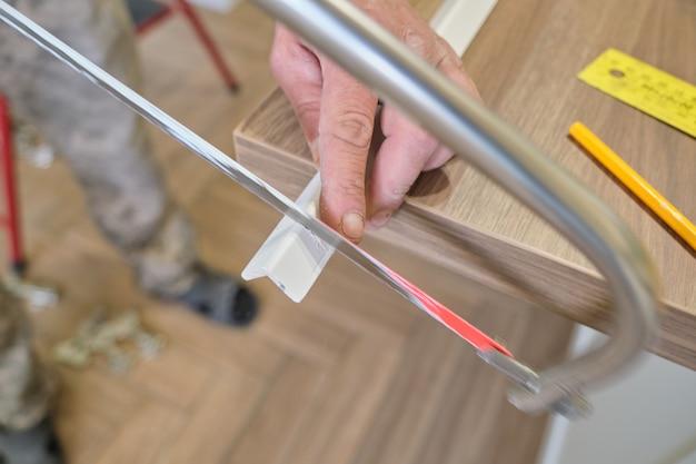 Reparação em casa, instalação e corte de cantos pintados de madeira