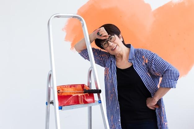 Reparação no apartamento. feliz mulher de meia-idade pinta a parede com tinta.