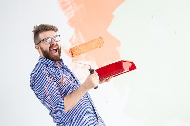 Reparação no apartamento. homem engraçado pinta a parede com tinta.