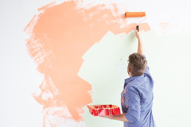 Reparação no apartamento. o homem pinta a parede com tinta. vista traseira. copie o espaço