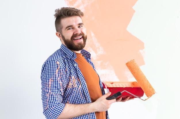 Reparação no apartamento. o homem pinta a parede com tinta.