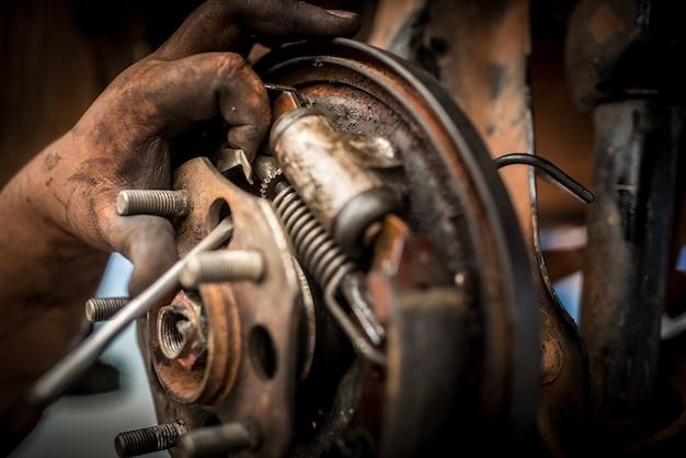 Reparação ou inspeção de freios de sistemas de freio e substituição de novas pastilhas de freio realizadas por mecânicos que trocam as pastilhas de carro em oficinas de reparo de automóveis