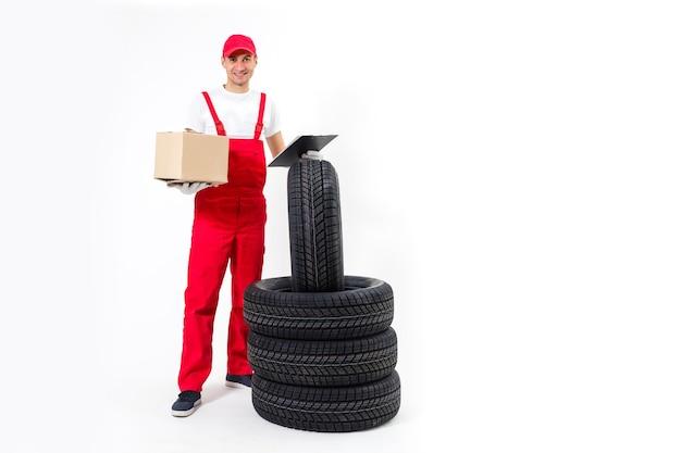 Reparador anotando o pedido: verificando a prancheta e empurrando o carrinho de pneus.