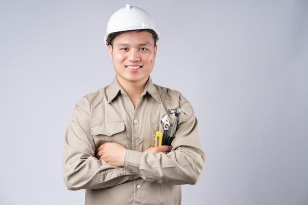 Reparador asiático em pé com os braços cruzados na cor cinza