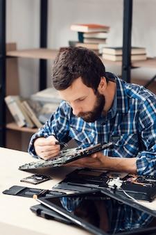 Reparador barbudo desmontando computador