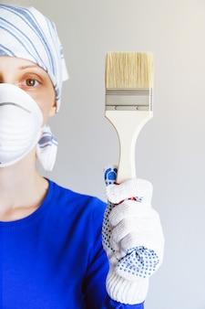 Reparador, carpinteiro, trabalhador assalariado, mulher ou menina em luvas de proteção e máscara detém um novo pincel limpo, parece na célula. o conceito de casa e reparação profissional, construção.