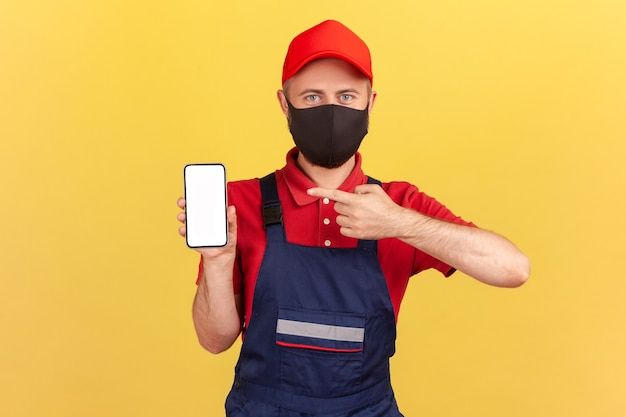 Reparador com máscara protetora no rosto apontando o dedo para smartphone com visor vazio