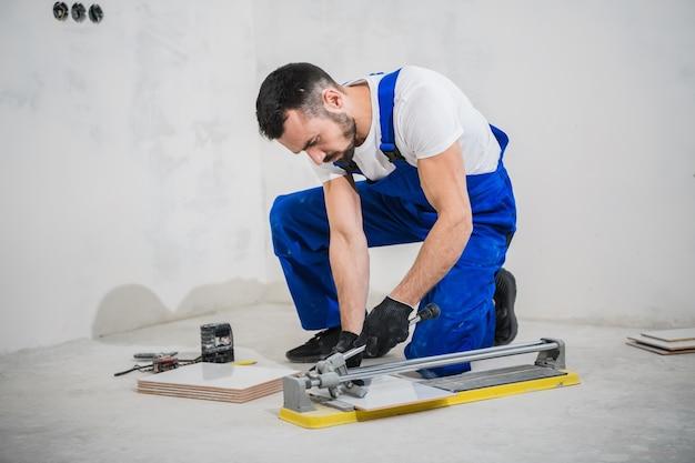 Reparador com roupa de trabalho azul usa um cortador de azulejos