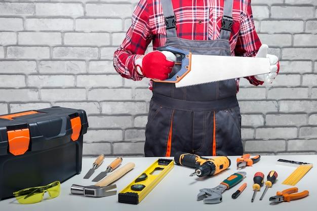 Reparador com serra manual e diferentes ferramentas na mesa de trabalho. conceito de bricolage e melhoramento da casa.