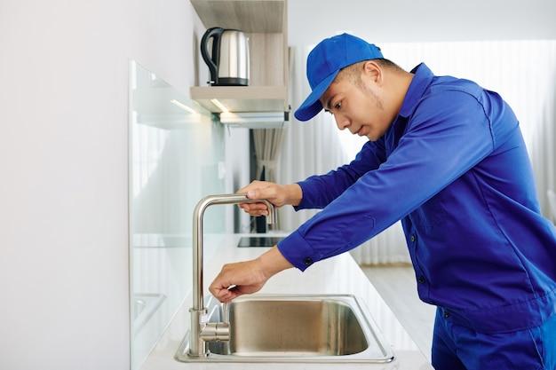 Reparador consertando torneira de água