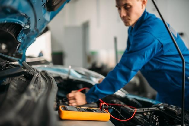 Reparador de automóveis com multímetro, inspeção de bateria