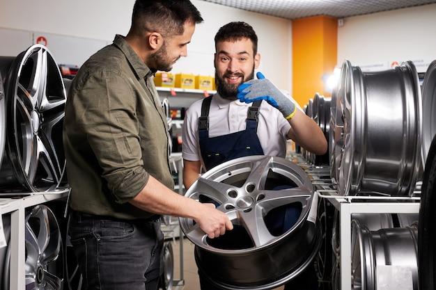 Reparador de automóveis falando sobre as características e vantagens da roda de carro para o cliente, eles têm uma discussão. na loja