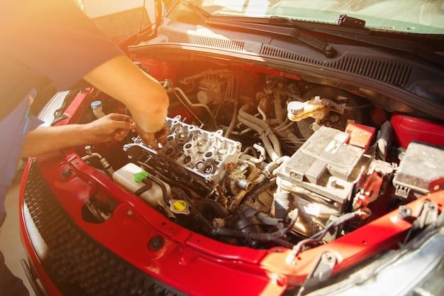 Reparador de automóveis profissional conserta um carro em uma estação de serviço e usa ferramentas especiais