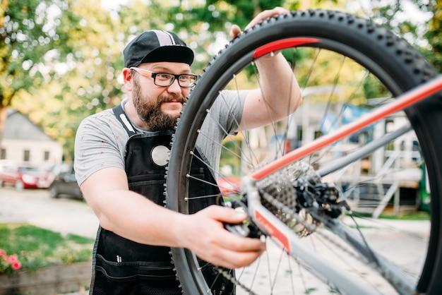 Reparador de bicicletas trabalha com roda de bicicleta, oficina de bicicletas ao ar livre. mecânico barbudo de avental