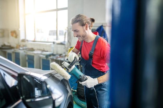 Reparador de homem barbudo sorridente com luvas de proteção moendo a carroceria do carro na garagem