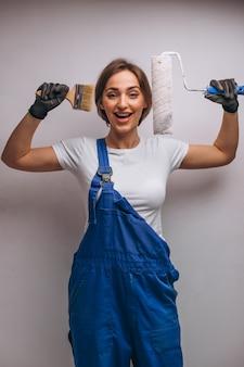 Reparador de mulher com rolo de pintura isolado