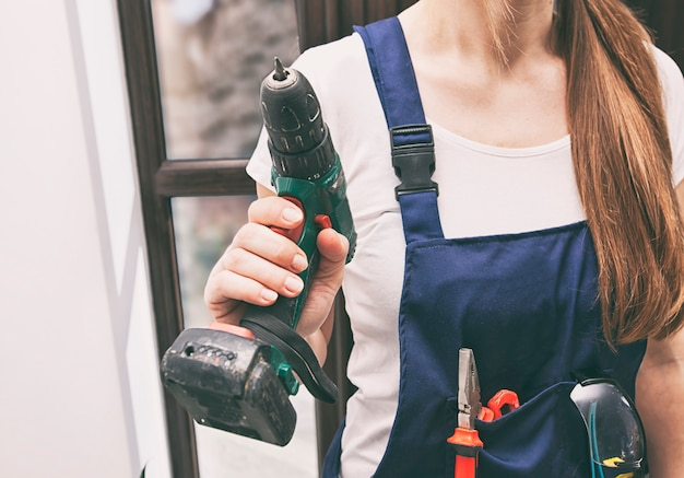 Reparador de mulher vestido com uniforme de trabalho em casa com chave de fenda e outros equipamentos na mão