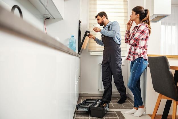 Reparador de pé e consertando fogão enquanto a dona de casa fica ao lado dele e o incomoda.