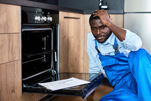Reparador de uniforme chateado, tendo problemas no trabalho enquanto conserta o forno, sente-se no chão tocando a cabeça, pensando em como resolver o problema, como consertar o forno elétrico na cozinha, em casa dentro de casa
