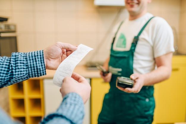 Reparador de uniforme dá o cheque ao cliente, faz-tudo.