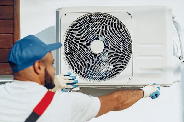 Reparador de uniforme, instalando a unidade externa do ar condicionado