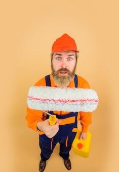 Reparador de uniforme surpreso segurando um reparador de rolo de pintura pintor profissional