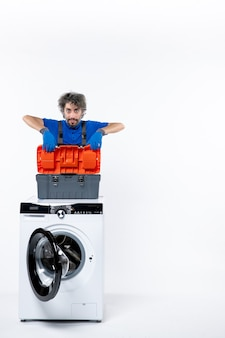 Reparador determinado de vista frontal colocando o saco de ferramentas na máquina de lavar no espaço em branco