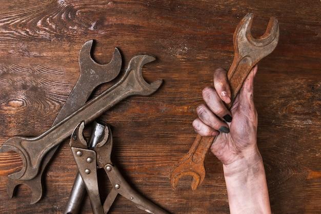 Reparador feminino. mão de uma mulher segurando uma chave inglesa e outras ferramentas deite-se sobre um fundo de madeira. conceito de feminismo e emancipação