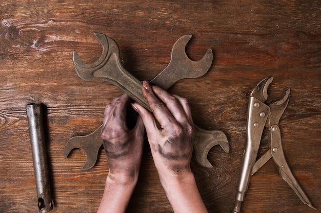 Reparador feminino. mão de uma mulher segurando uma chave inglesa e outras ferramentas deite-se sobre um fundo de madeira. conceito de feminismo e empoderamento