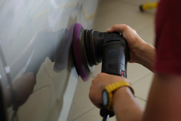 Reparador homem polindo carro com moedor especial close-up