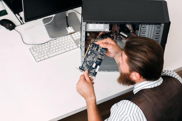 Reparador inspecionando microcircuito dentro da unidade de dvd. programador consertando computador desmontado no escritório, vista superior, espaço livre
