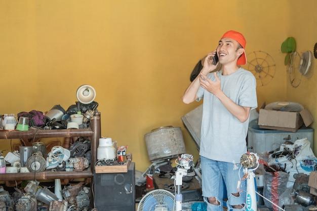 Reparador liga enquanto fica parado em volta das peças eletrônicas na oficina