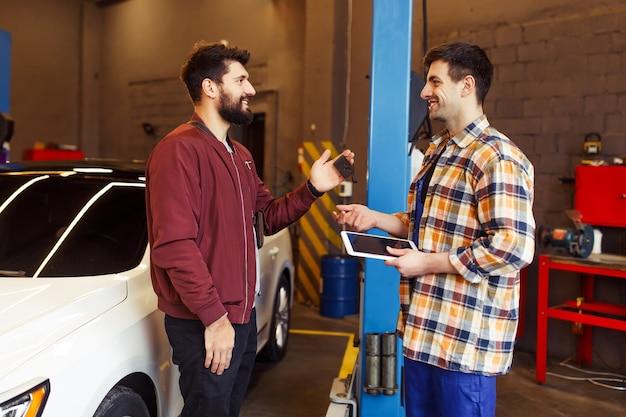 Reparador masculino sorridente segurando um tablet digital nas mãos e conversando com o cliente na oficina