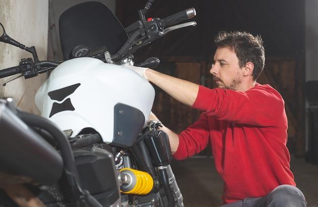 Reparador mecânico fazendo manutenção ou conserto, consertando a motocicleta, motocicleta, centro de serviço