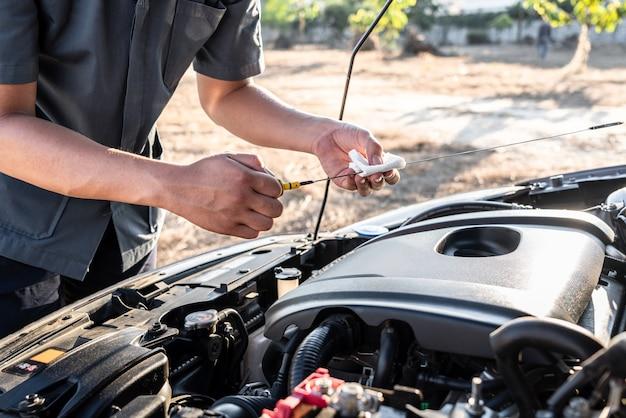 Reparador mecânico trabalhando em motores automotivos em serviço de reparo automotivo e verificando o óleo