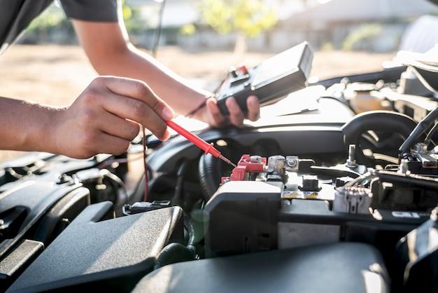 Reparador mecânico verificando motor automotivo em serviço de reparo de automóveis e usando bateria de teste de multímetro digital para medir vários valores e analisar, serviço e manutenção de verificação de bateria de carro