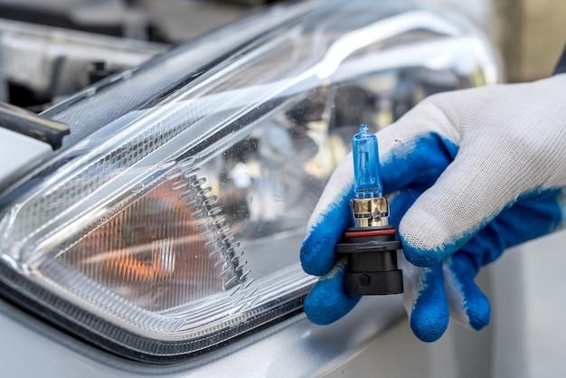 Reparador na oficina mostra lâmpada de carro novo para substituição, farol na superfície