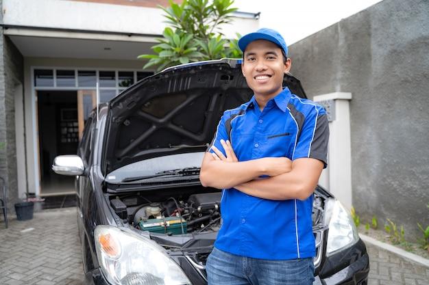 Reparador ou mecânico de automóveis cruzou o braço e olhando para a câmera
