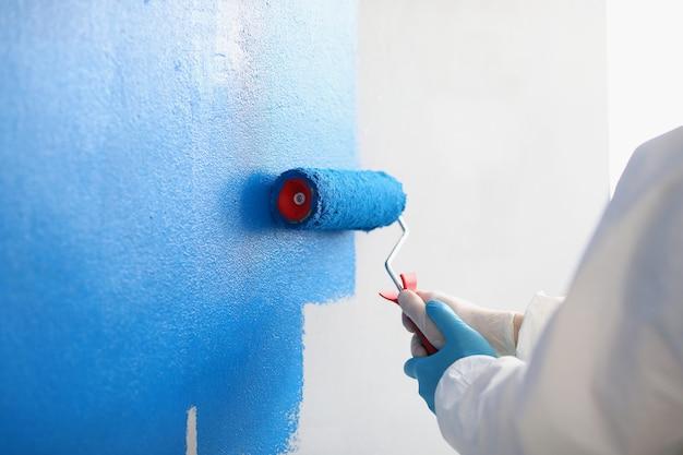 Reparador pintando uma parede branca em um apartamento azul usando o rolo close up