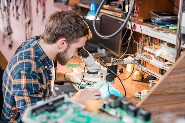 Reparador profissional de gadgets olhando no microscópio pelo local de trabalho enquanto tenta encontrar o problema do smartphone ou tablet