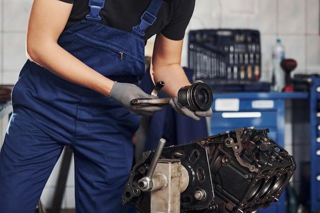 Reparador profissional na garagem trabalha com motor de automóvel quebrado
