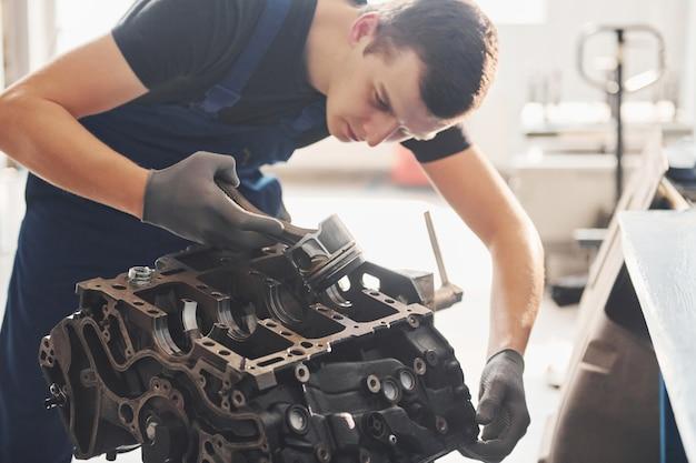 Reparador profissional trabalha com motor de automóvel quebrado