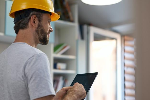 Reparador profissional usando capacete olhando para o lado usando um tablet digital enquanto fica dentro de casa