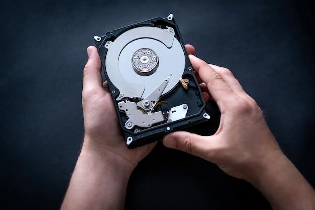Reparador segurando o disco rígido do computador nas mãos para consertar ou diagnosticar a vista superior