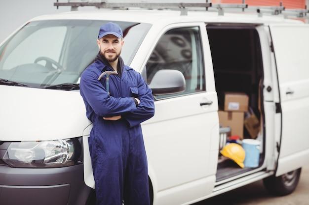 Reparador, segurando um martelo na frente de sua van