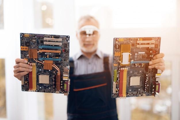 Reparador sênior está segurando duas placas-mãe.