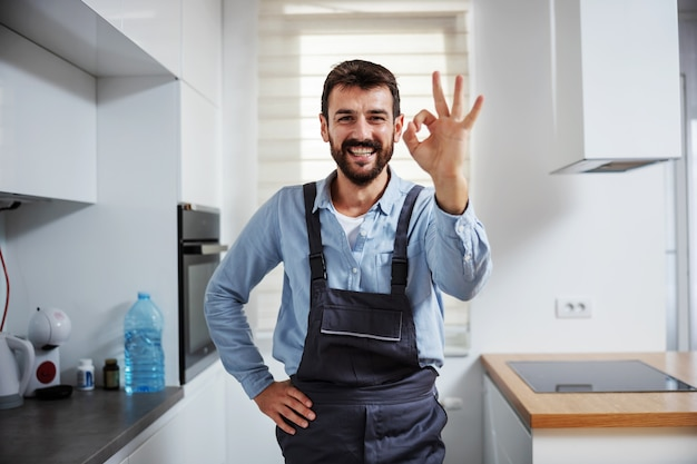 Reparador sorridente na cozinha e mostrando sinal de bom